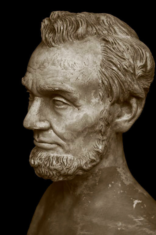 photo with black background of yellowed plaster cast bust sculpture of man with beard, namely Lincoln