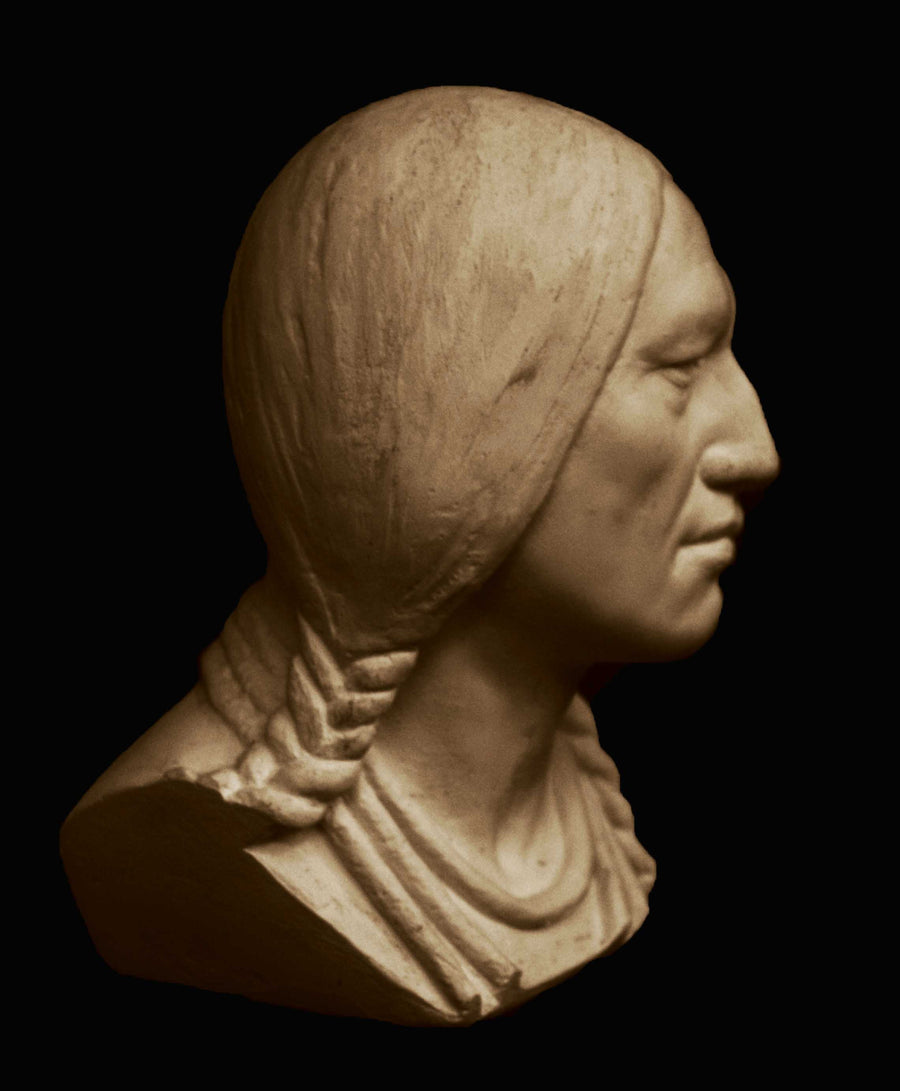photo with black background of plaster cast sculpture of male head of Massasoit with braids and necklaces