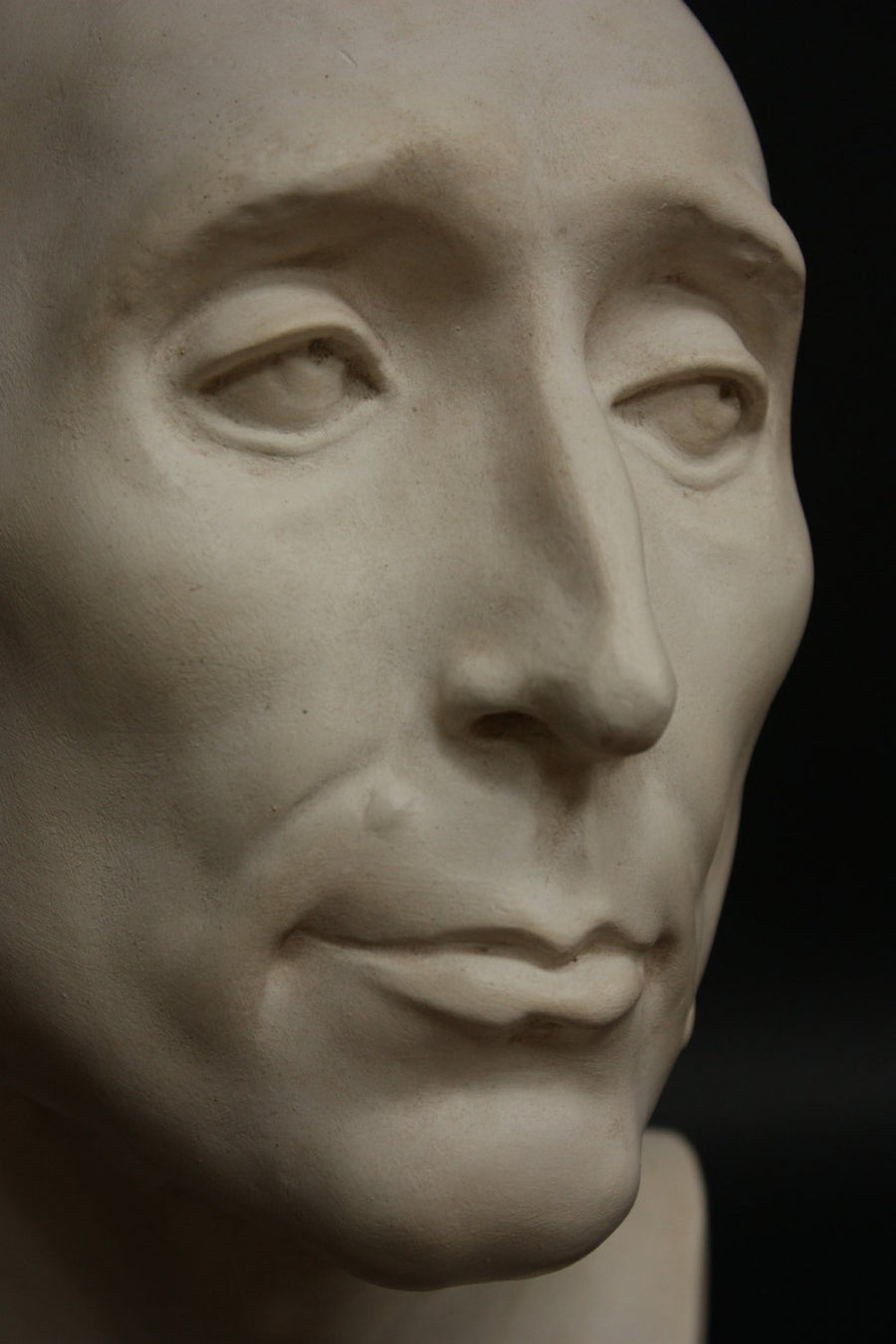 closeup photo with black background of plaster cast sculpture bust of man, namely Niccolo da Uzzano