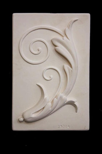 Photo of plaster cast sculpture relief of a study of a plant with scroll-like forms on a black background