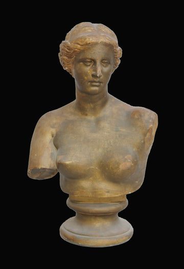 photo with black background of gold plaster cast bust and chest of woman, namely Venus