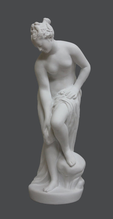 photo of plaster cast of sculpture of partially nude female, namely Venus, leaning forward to wash her left leg with a gray background
