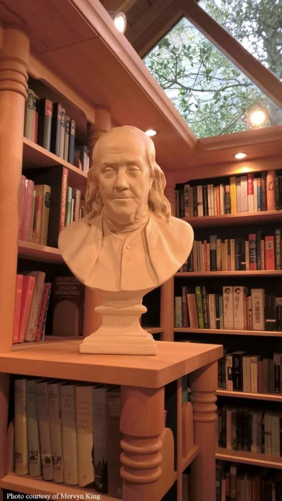 Photo of male bust sculpture on tall shelf with book shelves behind it