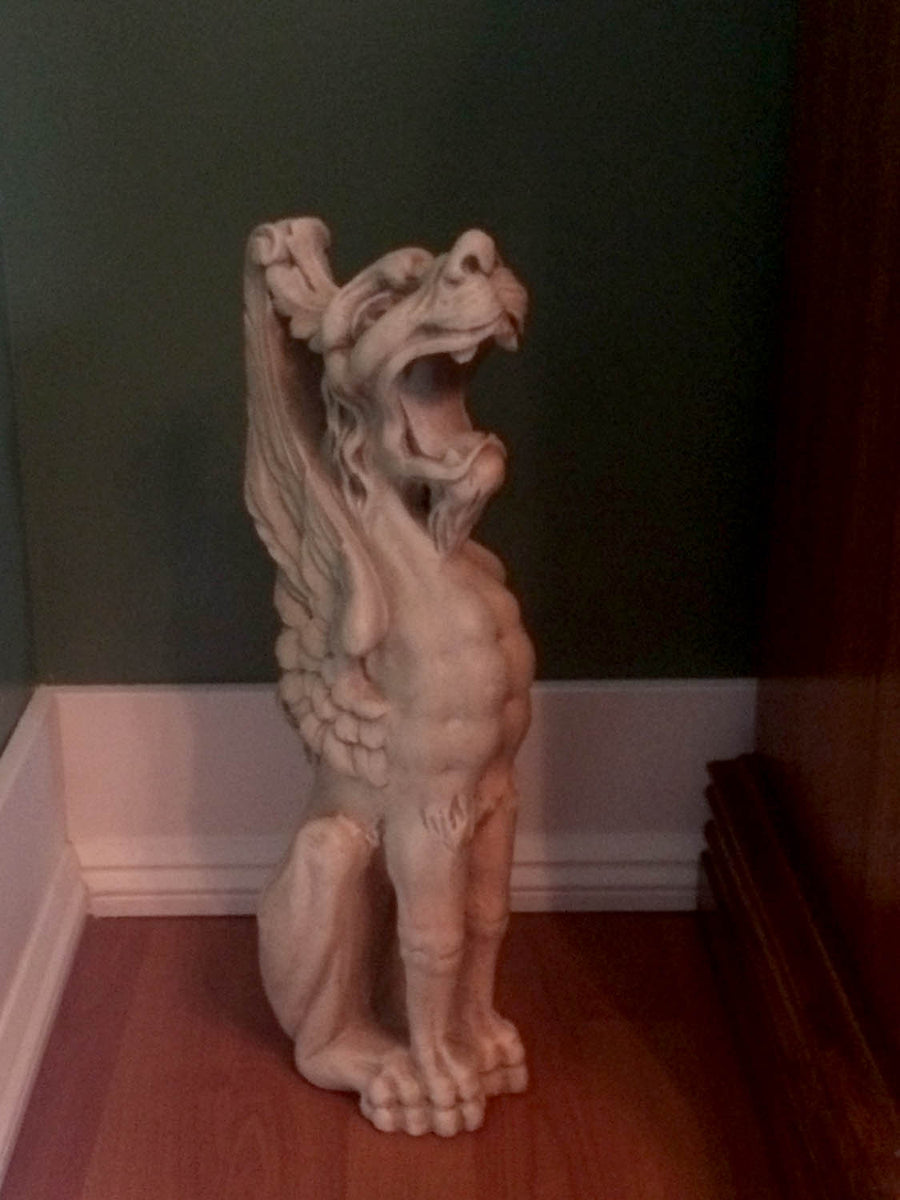 hoto of plaster cast sculpture of imaginary seated winged lion in front of a green wall with white baseboard