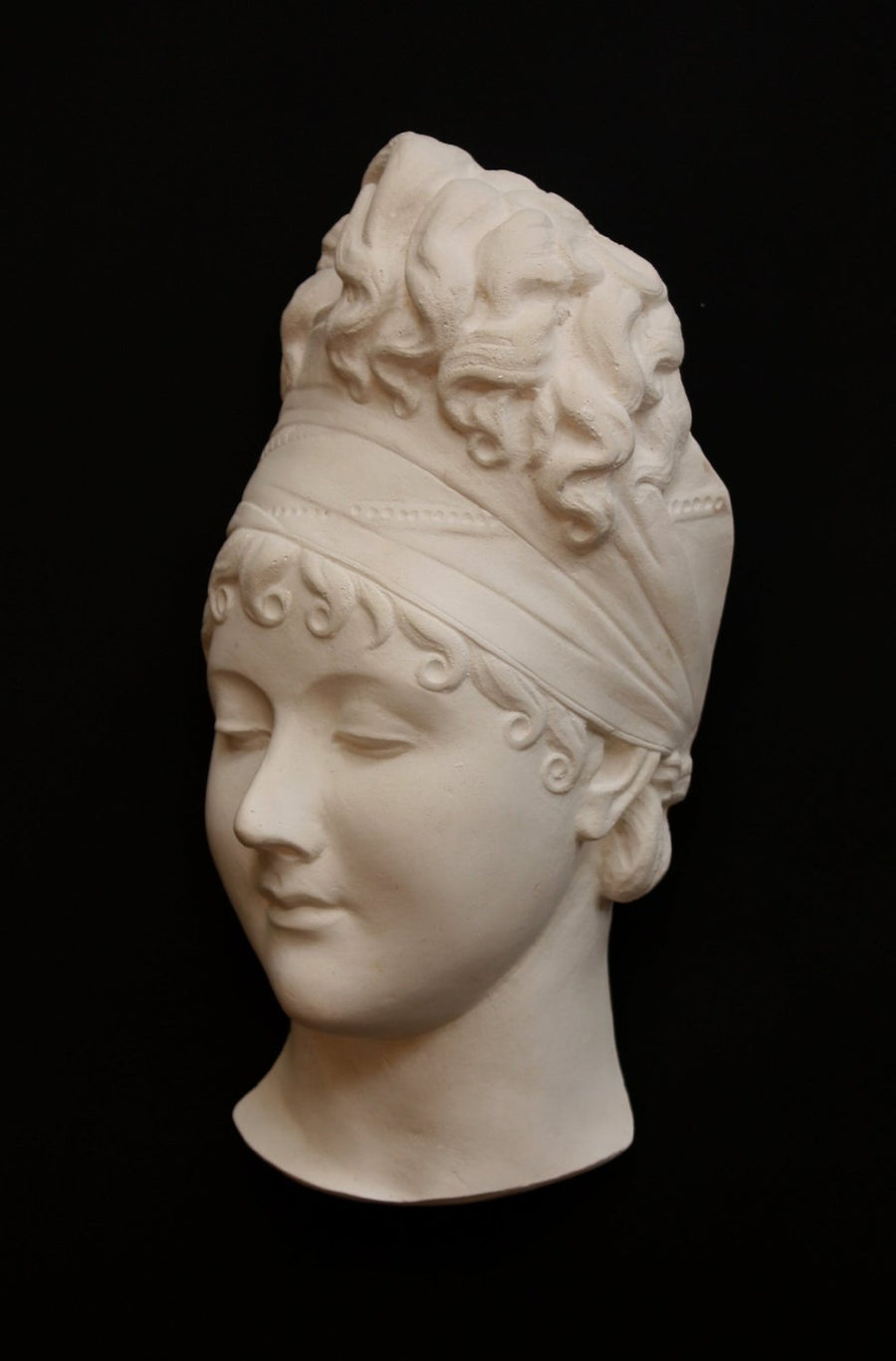 photo with black background of plaster cast sculpture of face of Madame Recamier with high up-do and ribbon over forehead