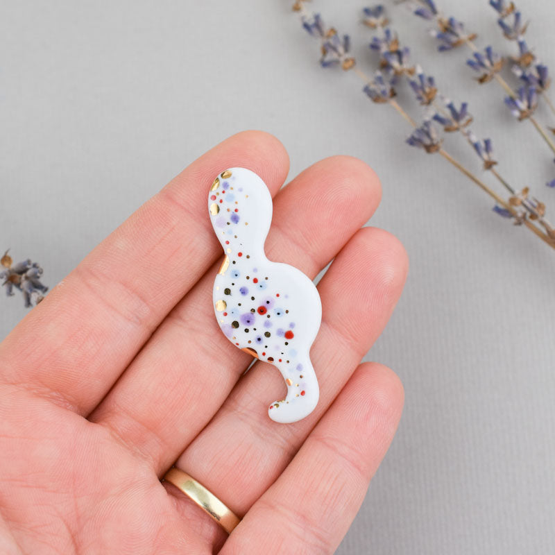 Porcelain brooch created and hand-painted by Vali Bondoc with high temperature ceramic dyes and colloidal gold.