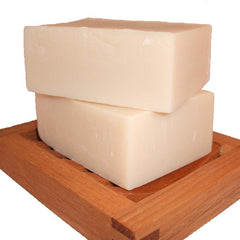 stack of two handmade soap bars on wooden soap dish