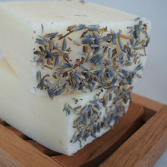 stack of two handmade lavender soap bars on wooden soap dish