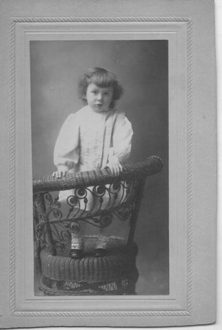 Black & white photo of a Victorian child stood on a wicker chair