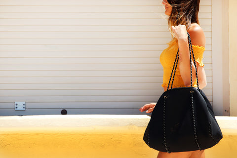 model in yellow top with a big bag