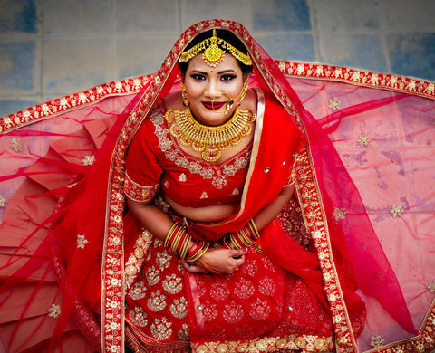 Image of a bride in red, by Ayrus Hill on Unsplash