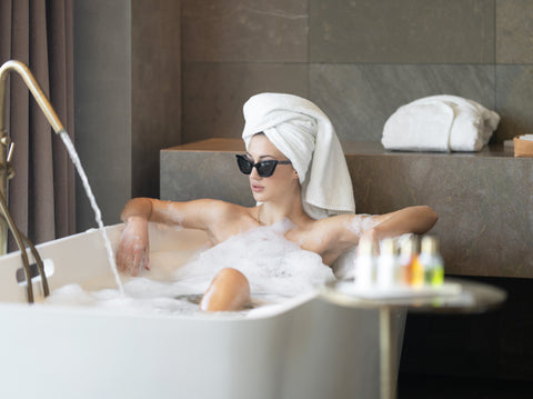 Model relaxes in a bubble bath with sunglasses and a hair towel