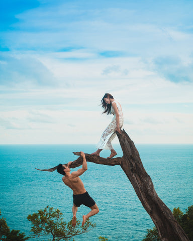 Lifestyle image of a couple playing in a tree near stunning sea