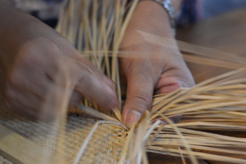Close up of hands weaving plants together