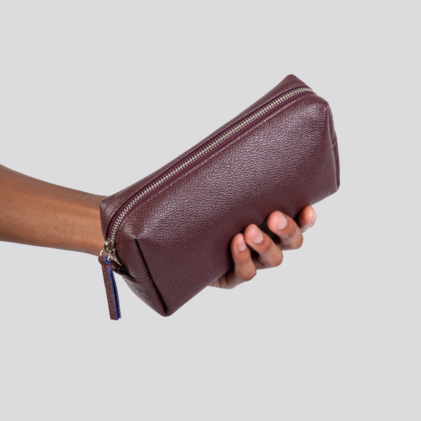 LUXTRA vegan toiletries bag, burgundy, held in hand