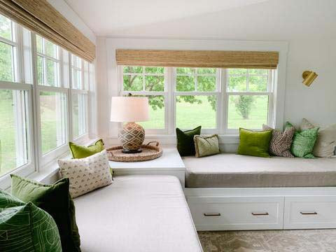 Two built in day beds with storage drawers, under windows with custom grey mattress covers, decorated with a selection of green and neutral throw pillows.