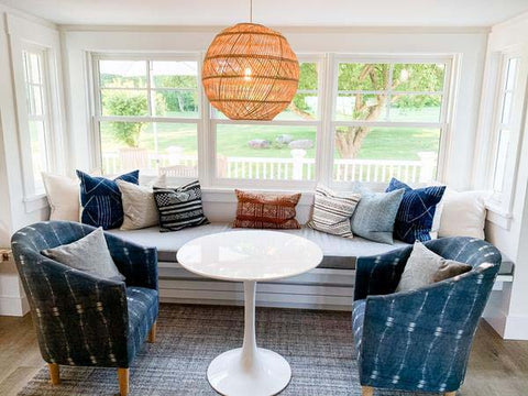 Kitchen window seat with rattan light, white tulip table and two blue mud cloth patterned chairs