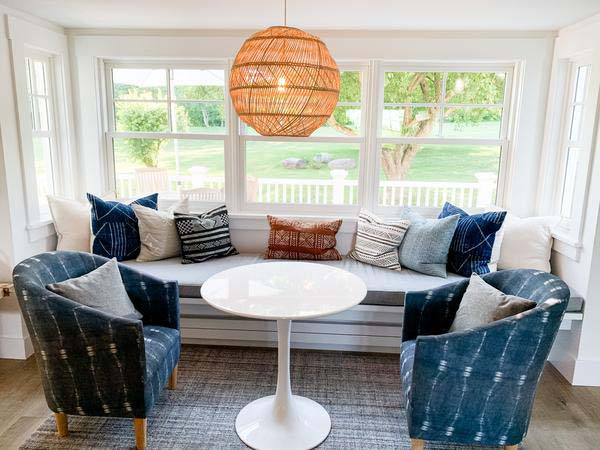 Kitchen nook with seating under a large window, decorated with custom grey cushion and a selection of vintage and new throw pillows. The kitchen nook is completed with a modern white round table and a blue accent chair on each end.