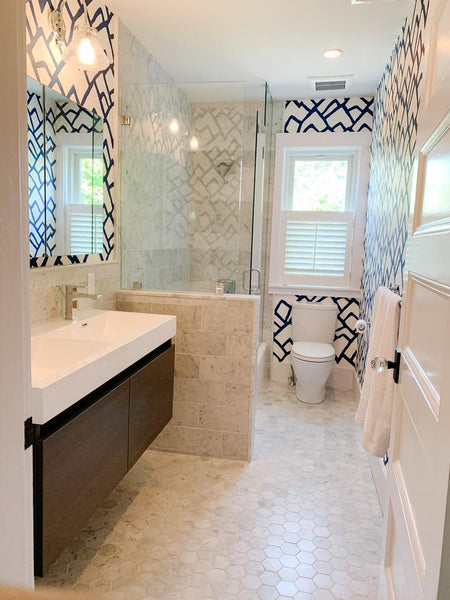 Modern bathroom with blue pattern wall paper, glass shower and floating double sink.