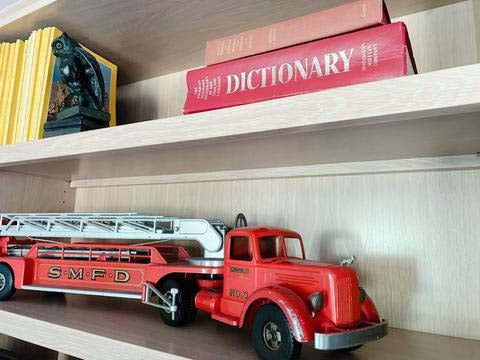 Shelves decorated with books and vintage red truck.