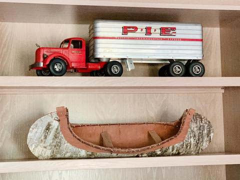 Shelves decorated with vintage red truck and birchbark canoe.