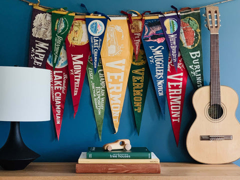 Boys room decorated with a  selection of colorful vintage pennants hung on the wall.