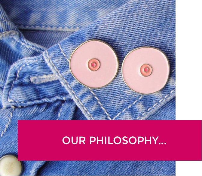 """Boob pins on a jean jacket with a banner that says """"our philosophy""""."""
