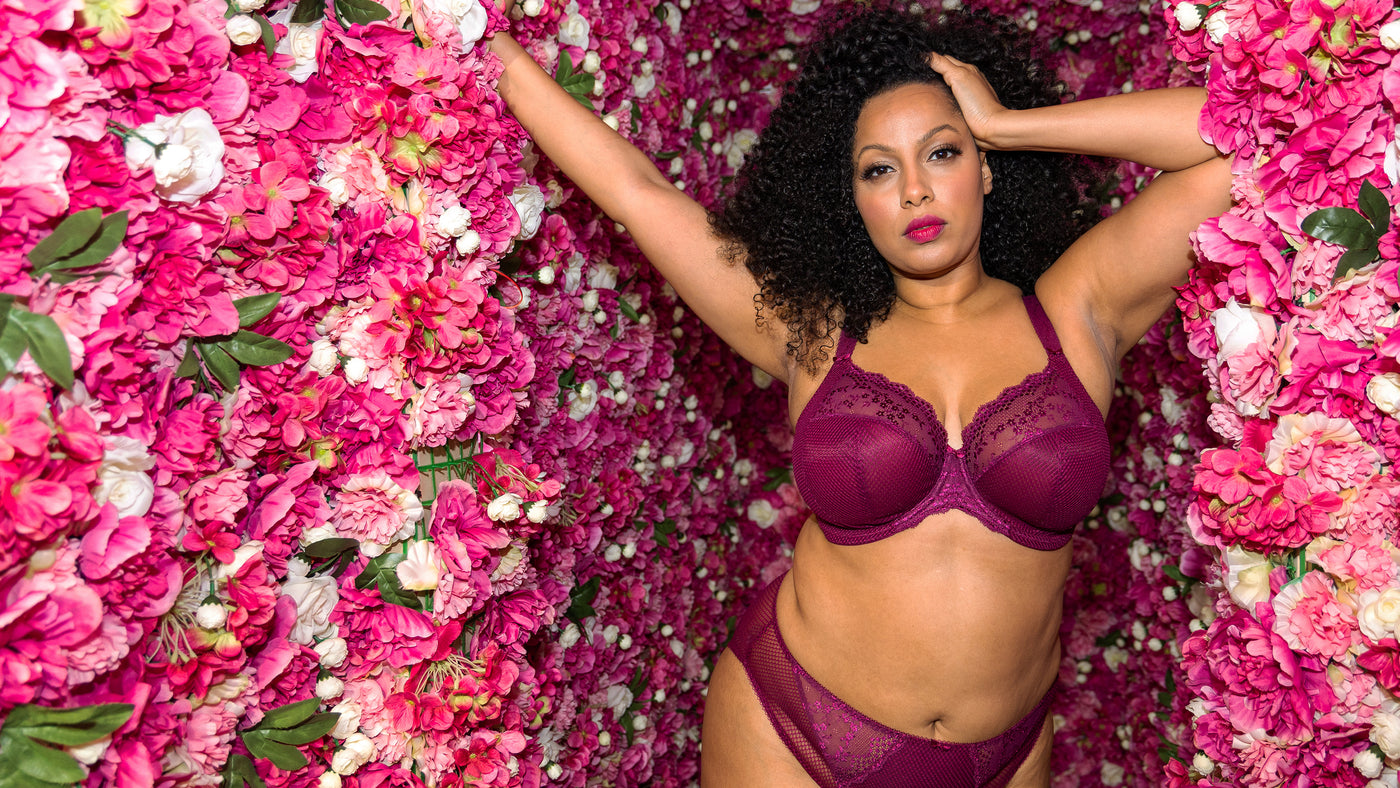 a plus size woman stands by a wall of pink flowers in a purple elomi charley bra.