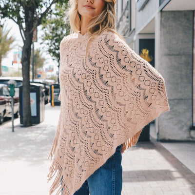 Blush color poncho with tassels has a scallop pattern throughout and is perfect for the spring.