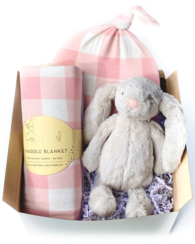 Curated gift set for baby girl includes a swaddle blanket, top knot hat, and snuggly baby bunny