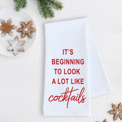 "White tea towel with red print that says, ""It's beginning to look a lot like cocktails""."