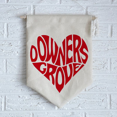 Downers Grove heart banner is made of canvas and has red letters.