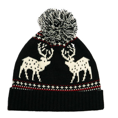 Festive winter hat with pom is black with ivory reindeer pattern and some hits of red.