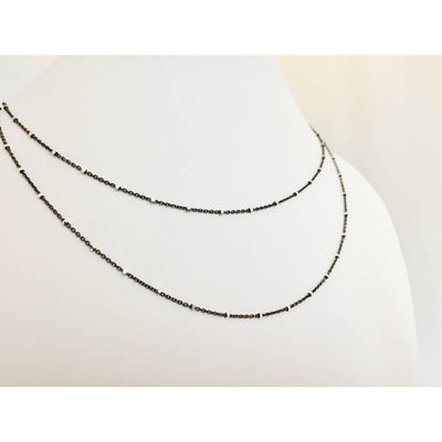 This minimalist necklace has 2 layers of dainty chain that is black rhodium with tiny silver bead accents. Chains measure 16 and 18 inches long