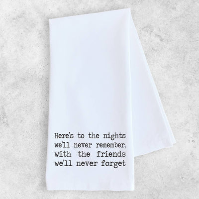 "White tea towel with black type that says, ""Here's to the nights we'll never remember with friends we'll never forget""."
