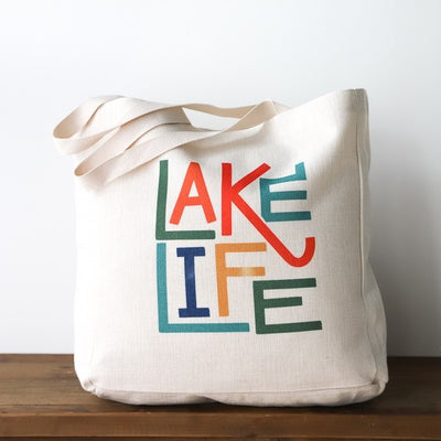 "Natural canvas tote that says ""lake life"" in colorful block letters"