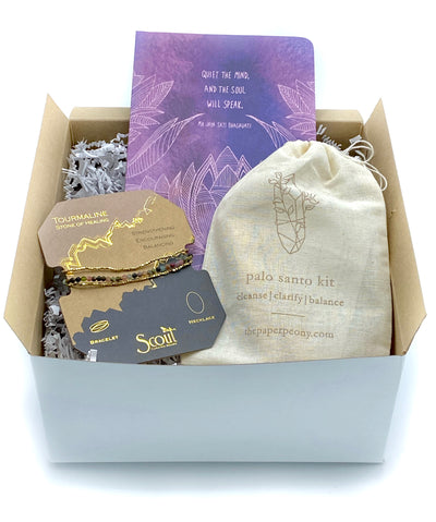 A gift set that contains a 5x8 lined journal, wrap bracelet with tourmaline, and palo santo incense sticks.