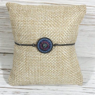 A colorful pave circle is the focal point on this simple gunmetal bracelet with sliding clasp