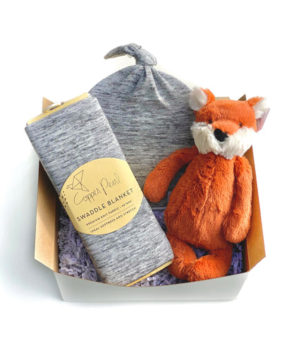 Neutral baby gift includes heather grey swaddle and top knot hat along with a sweet fox from Jellycat