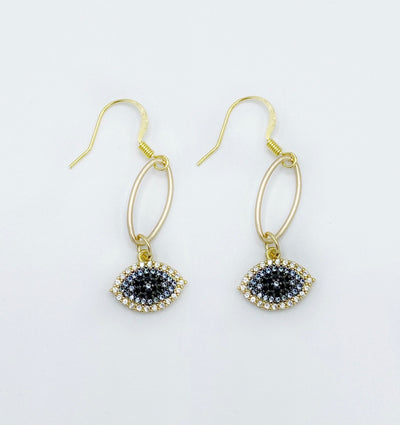 Gorgeous gold earrings with pave studded evil eyes dangling from a small gold oval link