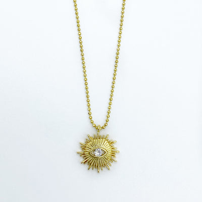 Dainty gold sunburst necklace with clear crystal evil eye on a gold faceted microball chain.