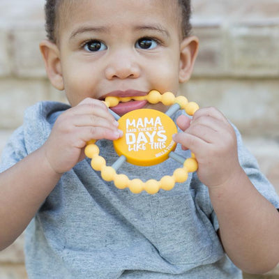 A toddler holding a soothing Bella Tunno silicone teether