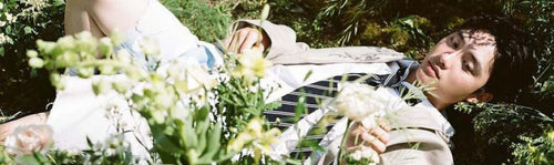d.o. do kyungsoo exo wearing a suit lying on a flower field solo album empathy image