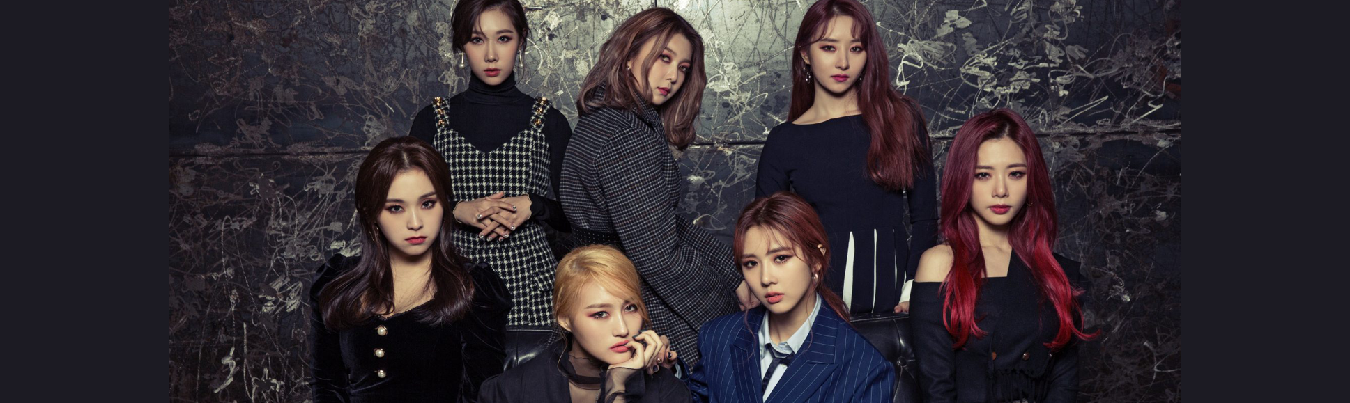 dreamcatcher members standing and sitting in front of a grey wall