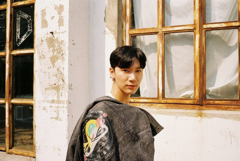 wayv  nct ten wearing a self designed jacket from his collection in front of an old house