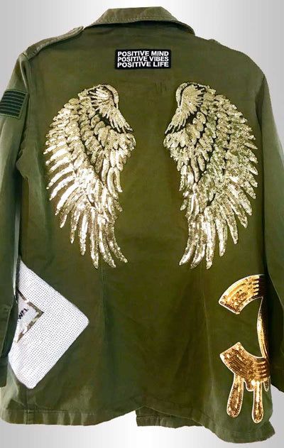 Army-green military jacket back donned with shiny gold wings and other embellishments.