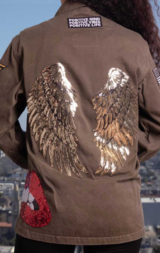 Female models back of CdJ Angel jacket with shiny gold wing appliques.