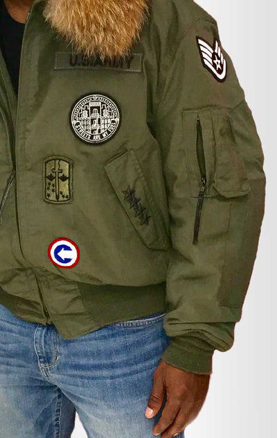 Male models front/side view of CdJ Furbomb jacket. Bomber-style army-green jacket with embellishments.