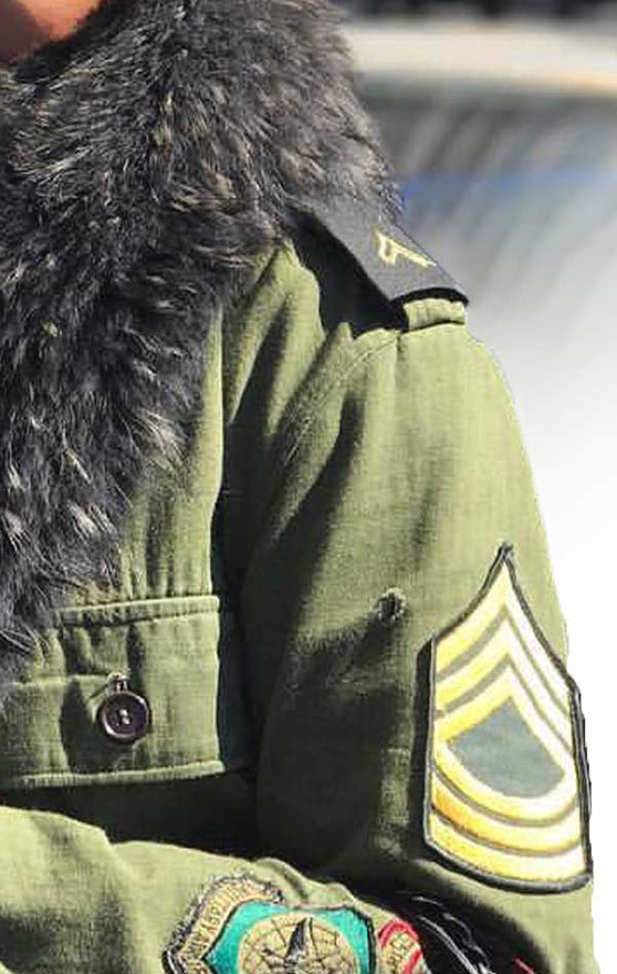 Armband of CdJ Furfly jacket with military-style embellishments and fur collar.