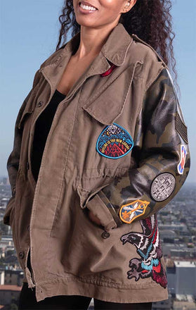 Load image into Gallery viewer, Female models front of CdJ Hides jacket in solid vest and leather camo sleeves with patch embellishments.